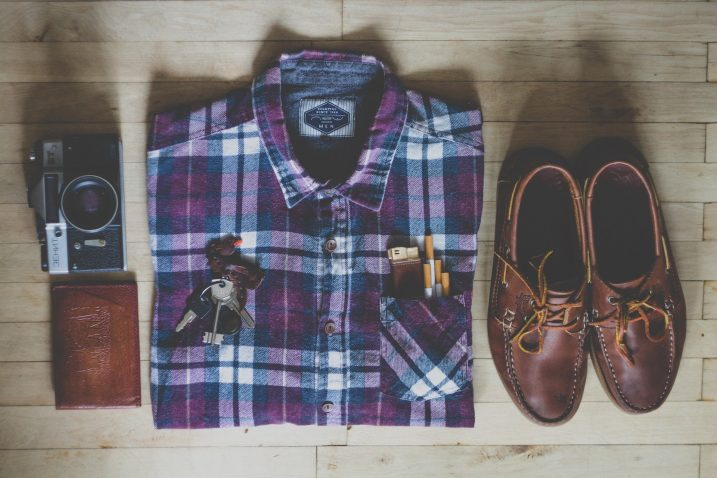 Shirt, shoes, keys and accessories ready to pack for a city break